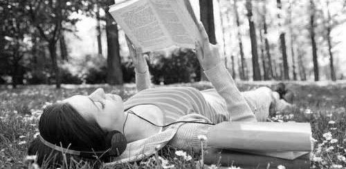 девушка читает книгу летом в парке